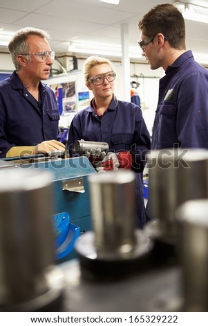 Engineer Working With Apprentices On Factory Floor - stock photo