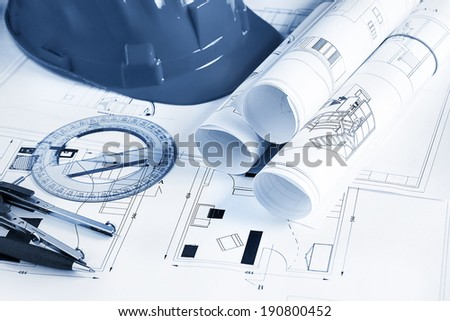 Engineer workplace with blueprints, compass, pen, protractor  and safety helmet - stock photo