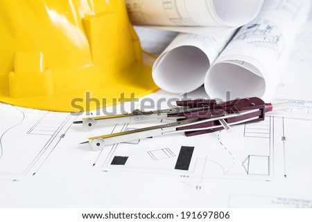 Engineer worplace with blueprints, compass  and safety helmet - stock photo