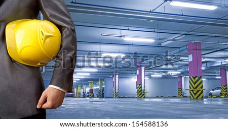 engineer yellow helmet for workers security against the background of underground parking for cars with the prospect Copy space for inscription  - stock photo