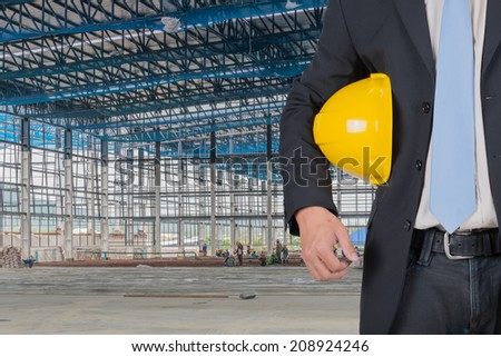 engineer yellow helmet for workers security against the support beams of the unfinished industrial workshop or room inside Copy space for inscription - stock photo