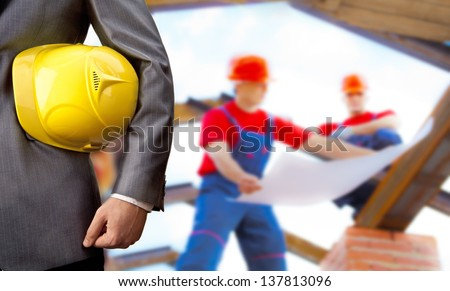 engineer yellow helmet for workers security on background of two construction workers are on the roof of the house with the construction plan in hand - stock photo
