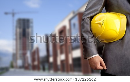 engineer yellow helmet for workers security on the background of a new high-rise apartment buildings and construction cranes and blue cloudy sky - stock photo