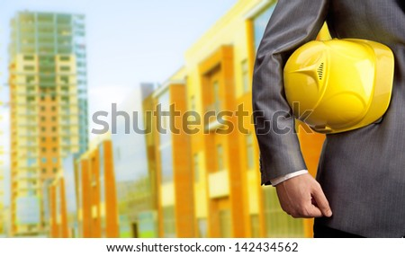engineer yellow helmet for workers security on the background of a new high-rise apartment buildings evening sunset sky - stock photo
