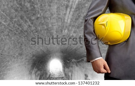 engineer yellow helmet for workers security over the gray tunnel at the prospect of leaving