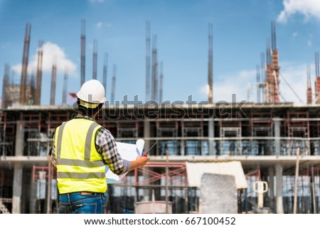 Engineering consulting people on construction site stock photo 100 engineering consulting people on construction site holding blueprint in his hand building inspector construction malvernweather Gallery