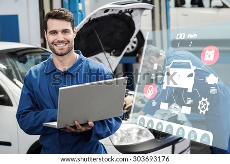 Engineering interface against smiling mechanic using a laptop - stock photo