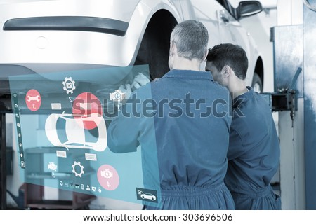 Engineering interface against team of mechanics working together - stock photo