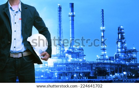 engineering man and safety helmet standing against oil refinery plant in heavy petrochemical industry estate - stock photo