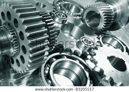 engineering parts arrangement, blue toning concept, focal-point on the large closest gear - stock photo