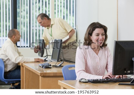 Engineering student working at computer station with professor and student in background - stock photo