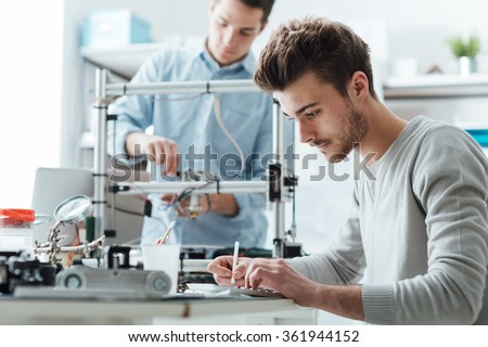 Engineering students working in the lab, a student is using a 3D printer in the background - stock photo