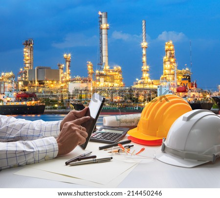 engineering working on computer tablet  against beautiful oil refinery background - stock photo