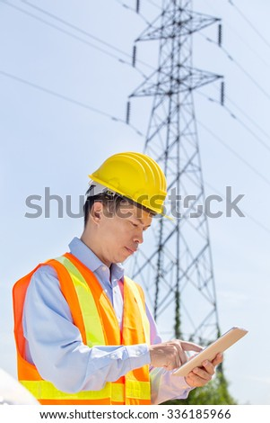 Engineering working on High-voltage tower, working on digital tablet