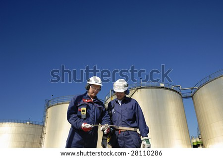 engineers and sunlit oil storage tanks, shot from a low-angle - stock photo