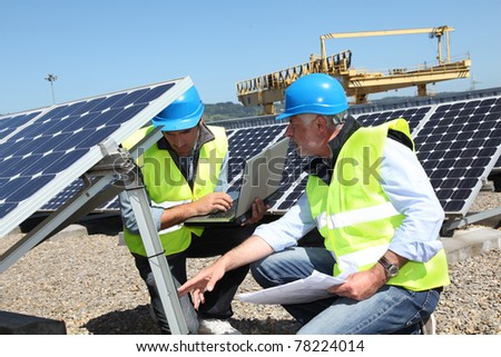 Engineers checking solar panels running - stock photo