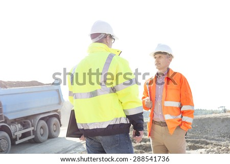 Engineers discussing at construction site against clear sky on sunny day - stock photo