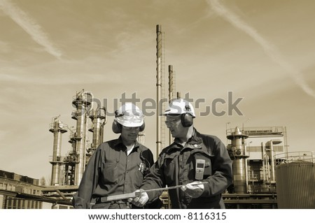 engineers in front of large oil refinery, background in toning concept - stock photo