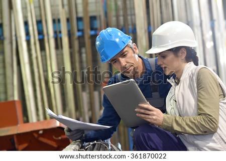 Engineers in metallurgy warehouse using digital tablet - stock photo