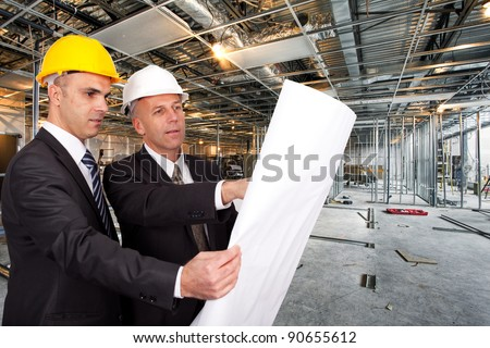 Engineers looking at a plan on a construction site - stock photo