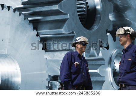 engineers, mechanics with large cogs and gears machinery - stock photo