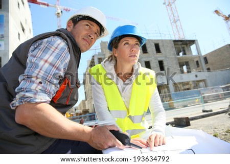 Engineers on building site checking plans - stock photo