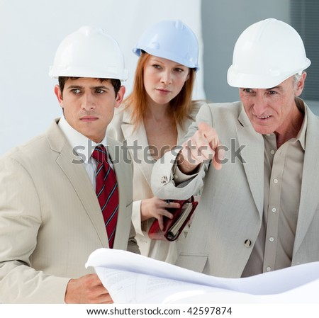 Engineers studying blueprints in a building site - stock photo