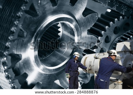 engineers, workers with giant cogwheel and gears machinery, metal indutry - stock photo