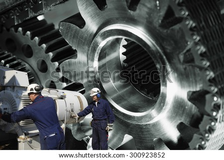 engineers, workers with machinery, large cogwheels and gears in background, focal-point on workers - stock photo