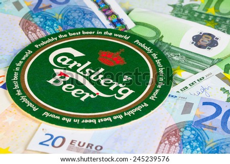 England, London - November 11, 2014:Beermat from Carlsberg beer and eur money.The Carlsberg is a Danish brewing company founded in 1847 by J. C.Jacobsen with headquarters located in Copenhagen,Denmark - stock photo