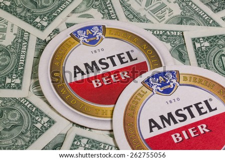 England,London - November 11, 2014:Beermats from Amstel beer and US dollars. Amstel Brewery is a Dutch brewery founded in 1870 on the Mauritskade in Amsterdam - stock photo