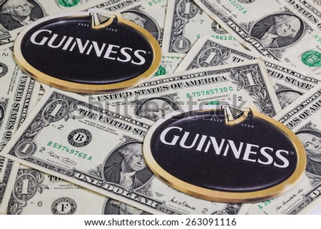 England,London - November 11,2014:Beermats from Guinness beer and US dollars.Guinness is an Irish dry stout that originated in the brewery of Arthur Guinness (1725�¢??1803) at St. James's Gate, Dublin. - stock photo