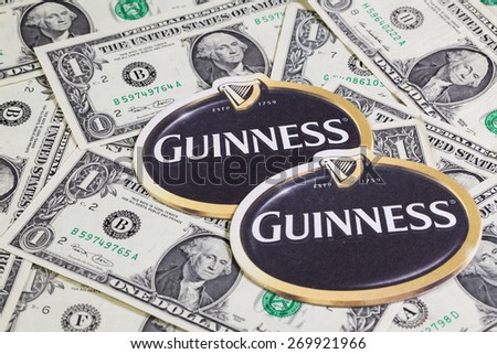 England,London - November 11, 2014:Beermats from Guinness beer and US dollars.Guinness is an Irish dry stout that originated in the brewery of Arthur Guinness (1725�¢??1803) at St. James's Gate,Dublin. - stock photo