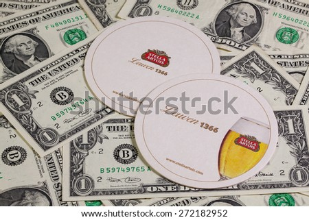 England,London - November 11, 2014:Beermats from Stella Artois and US dollars.It has been brewed in Leuven, Belgium, since 1926.Stella Artois is one of the prominent brands of Anheuser-Busch InBev - stock photo