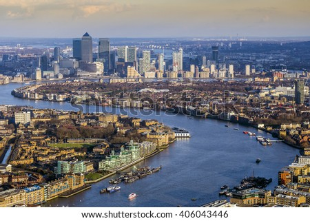 England, UK - Aerial skyline view of east London with River Thames and the skyscrapers of Canary Wharf at background