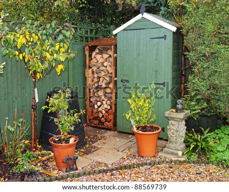 English back garden in Autumn with shed and log store - stock photo