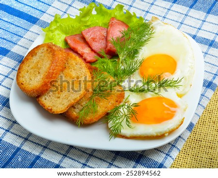 English breakfast - toast, egg, bacon and salad, sacking background. - stock photo