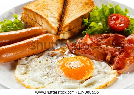 English breakfast - toast, egg, bacon and vegetables on white background - stock photo