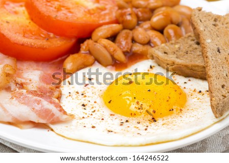 English breakfast with fried eggs, bacon and beans, close-up - stock photo