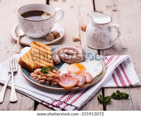 English breakfast with fried eggs, bacon, sausages, beans, toasts. selective focus. - stock photo