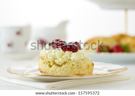 English Cream tea scene with scones, Devonshire style, on china plate with cake stand behind. Part of a series showing the preparation of scones. - stock photo