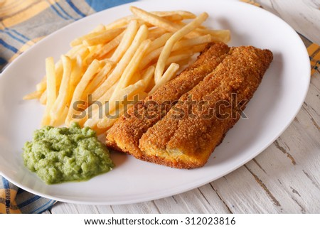 English food: fish in breadcrumbs with fried potatoes and pea puree close-up on a plate. horizontal