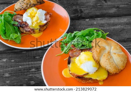 English muffin with bacon, egg benedict with hollandaise sauce and arugula salad - stock photo