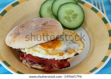 English muffin with fried egg and bacon  - stock photo