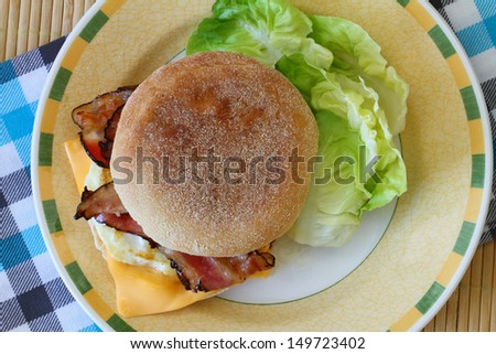 English muffin with fried egg, bacon and cheese - stock photo