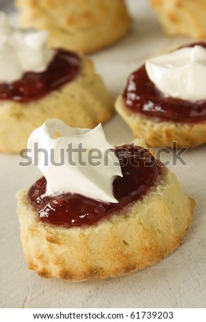English scones topped with jam and whipped  fresh cream - stock photo