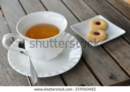 English tea in white cup with cookie on wooden table. - stock photo