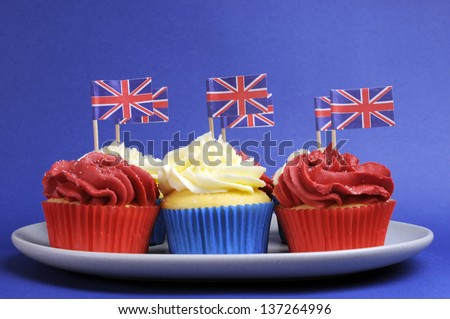 English theme red, white and blue cupcakes with Great Britain Union Jack flags for Queens Birthday weekend and national holiday party celebrations. - stock photo