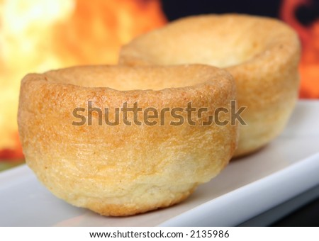 English yorkshire pudding, traditionally eaten with roast beef, macro on white plate by fire and flames - stock photo