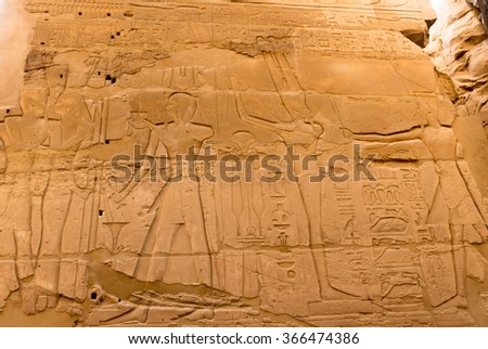 Engraved figure of Egyptian god and Pharaoh on the wall in the Temple of Karnak, Luxor, Egypt - stock photo